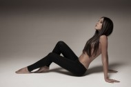 Gorgeous young woman posing in studio wearing black leggings