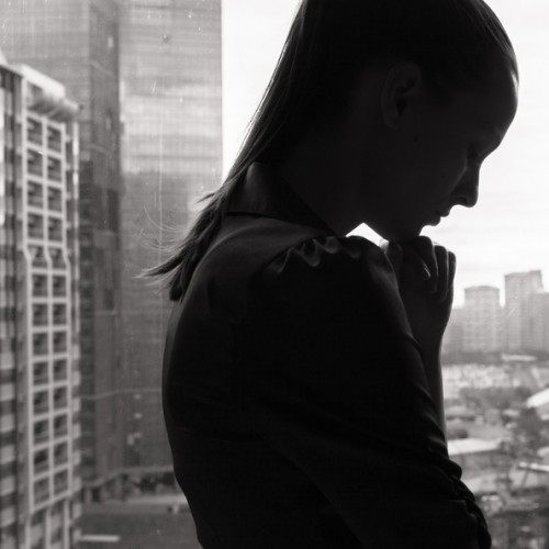 Black silhouetted woman looking pensive